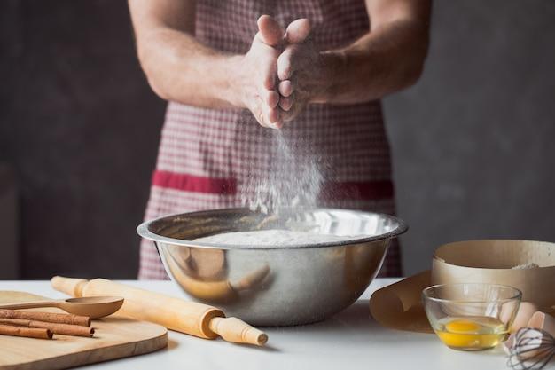 素朴なキッチンで一握りの小麦粉と卵。男性の手の壁に生地をこねる