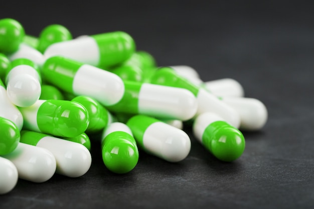 Горсть зеленых и белых капсул пилюль на черном фоне. фармацевтика, лекарства, витамины, наркотики, экстази