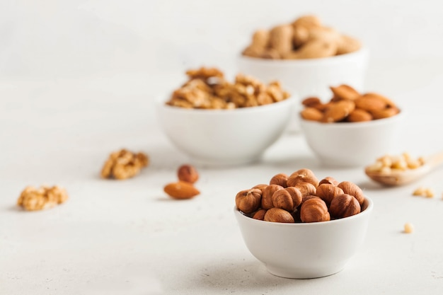 白いボウルにヘーゼルナッツの一握り、明るい背景にナッツの盛り合わせ。健康的なスナック、健康的な脂肪。スペースをコピーします。