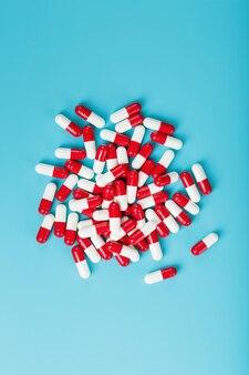 青の背景に赤と白の錠剤カプセルの一握り。空き領域上面図