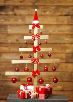 手作りのクリスマスツリーと木製の壁にプレゼント