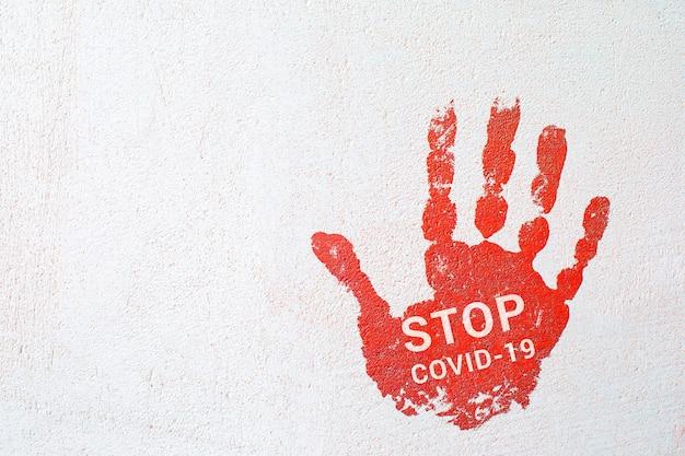 가벼운 콘크리트 벽에 stop covid19라는 문구가있는 손자국