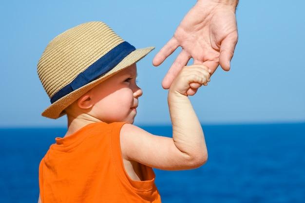Руки ребенка и родителя на отдыхе у моря.
