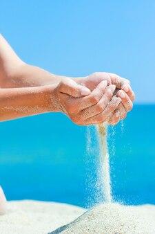 A hands는 여행 중에 자연에 바다에서 모래를 붓습니다. 바다 모래 시간의 휴가가 지나갔다.