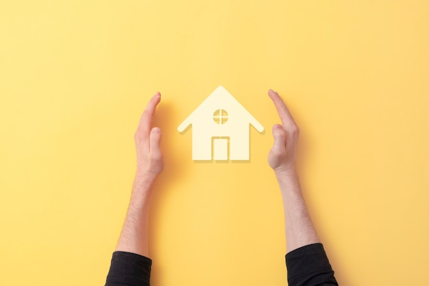 Руки защищают значок дома, концепция безопасности недвижимости
