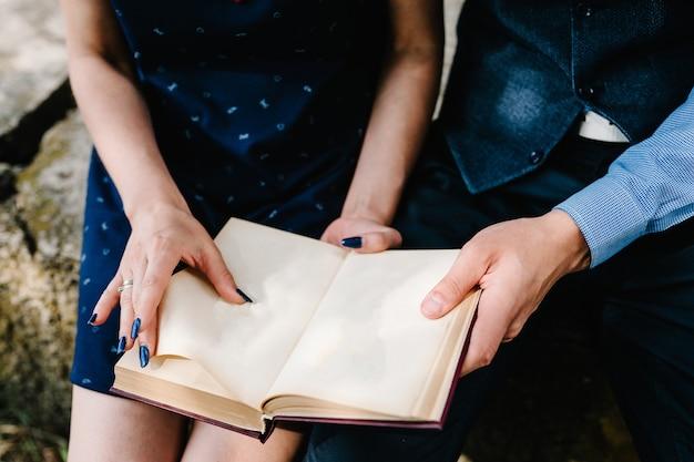 座っている若いカップルが膝の上に開いた本を読む手