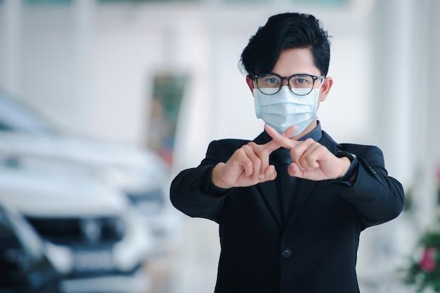 Красивый азиатский бизнесмен в офисе продаж автомобилей, он болен и носит маску, работая над бизнес-концепциями.