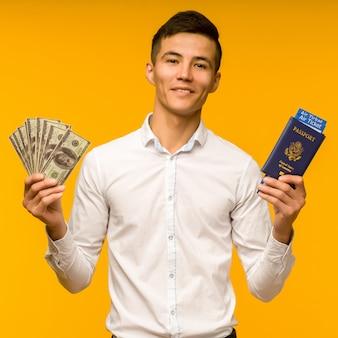 白いシャツを着たハンサムなアジア人男性が宝くじに当選することを喜んでいます。彼は黄色いスペースに航空券とお金のドルが入ったパスポートを持っています。