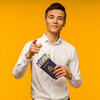 흰 셔츠를 입은 잘 생긴 아시아 남자가 복권에 당첨되어 기뻐합니다. 그는 노란색 배경에 항공권과 돈 달러가있는 여권을 들고 카메라를 가리키고 있습니다. -이미지