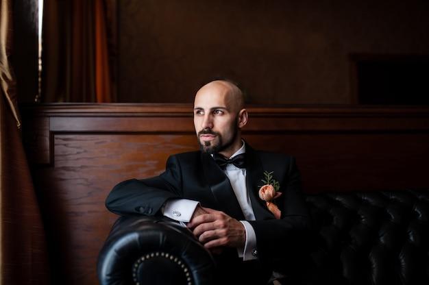 Красивый лысый мужчина в черном костюме
