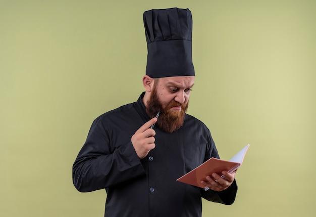 Красивый бородатый шеф-повар в черной униформе держит карандаш и смотрит в блокнот на зеленой стене