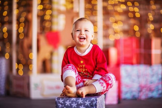 Красивый белокурый мальчик в рождественской пижаме сидит на подарочной коробке. рождественский фон. фото высокого качества