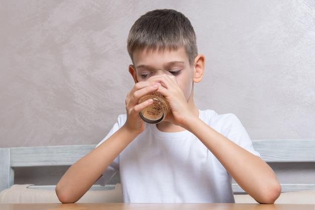 Красивый мальчик пьет газированную воду из стакана, крупным планом, копией пространства. концепция нездоровой пищи, любимая еда детей