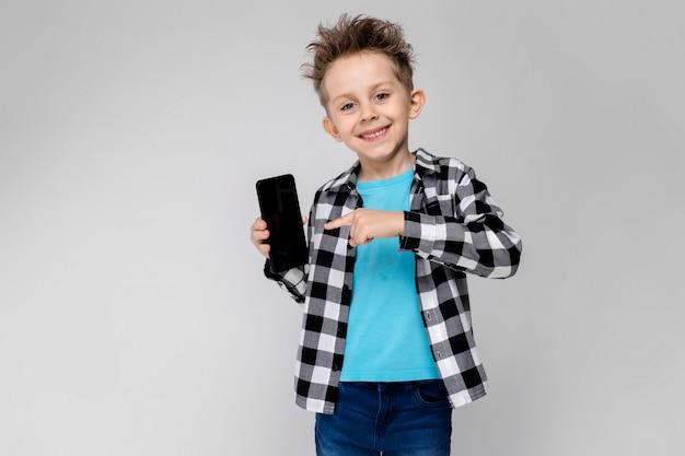 Красивый мальчик в клетчатой рубашке, синей рубашке и джинсах показывает мобильный телефон