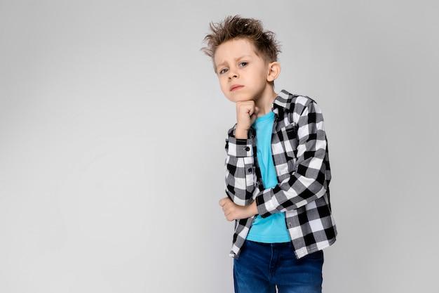 Стоит красивый мальчик в клетчатой рубашке, синей рубашке и джинсах