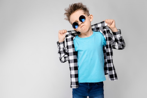 Красивый мальчик в клетчатой рубашке, синей рубашке и джинсах стоит на сером фоне. мальчик носит круглые очки. рыжий мальчик держит пальцами воротник рубашки
