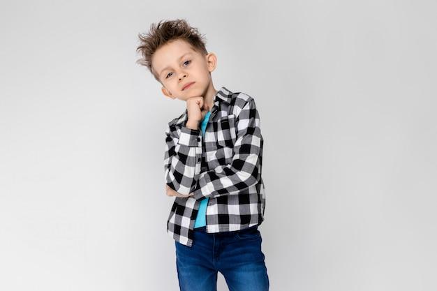 Красивый мальчик в клетчатой рубашке, синей рубашке и джинсах стоит на сером фоне. мальчик поддерживает подбородок рукой