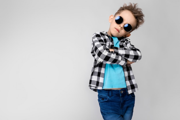 Стоит красивый мальчик в клетчатой рубашке, синей рубашке и джинсах. мальчик носит круглые очки. рыжий мальчик сложил руки на груди