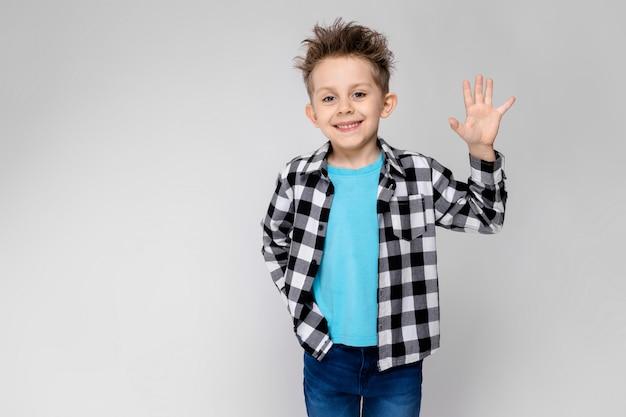 Красивый мальчик в клетчатой рубашке, синей рубашке и джинсах стоит