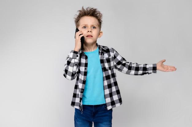 Красивый мальчик в клетчатой рубашке, синей рубашке и джинсах разговаривает по телефону