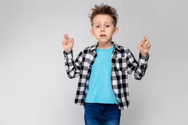 Красивый мальчик в клетчатой рубашке, синей рубашке и джинсах