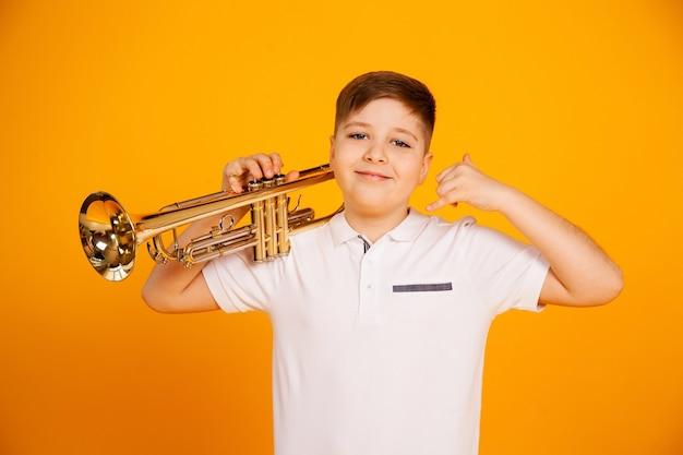 Красивый мальчик в белой футболке держит трубку на плите. мальчик с трубкой показывает жест рукой.