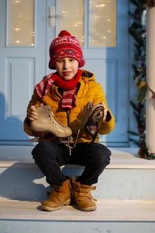 明るい服を着たハンサムな男の子が家のポーチに座って、古いスケート靴を持っています。