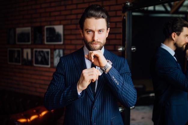 手に時計を持ってカメラを見ているハンサムなビジネスマン。
