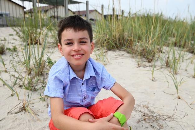 Красивый ребенок сидит на песчаном грунте в позе лотоса и улыбается, глядя в камеру на фоне природы. концепция расслабления, безмятежности и благополучия.