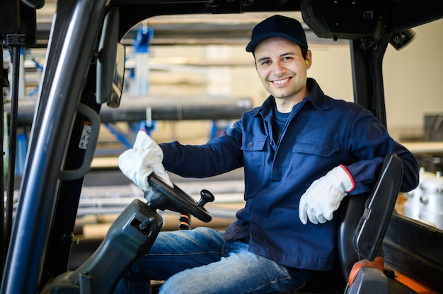 Красивый рабочий-строитель управляя грузоподъемником в промышленном предприятии