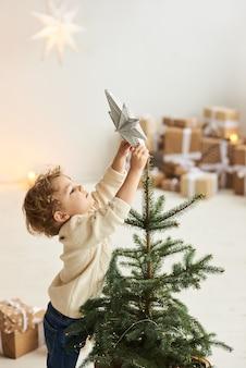 ハンサムな巻き毛の小さな男の子がクリスマスツリーを飾りました