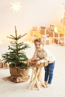 Красивый кудрявый мальчик сидит на деревянном стуле возле елки