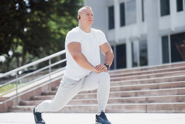 Красивый фитнес-мужчина в спортивной одежде, делает растяжку во время подготовки к серьезным упражнениям в современном городе