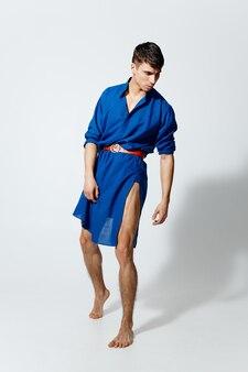 Красивый гей в голубом платье танцует на светлом фоне