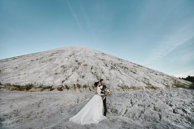 잘 생긴 신랑과 젊은 신부 백그라운드에서 산들과 야외 결혼식 전에 포즈.