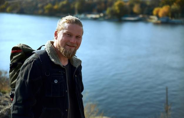 崖の端に笑みを浮かべて立っているハンサムな腰の冒険家。美しい秋の風景と湖。自然の中を旅する人々の概念。