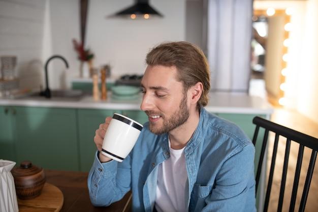 Красивый мужчина пьет утреннюю чашку чая