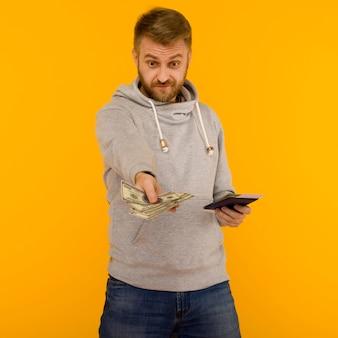灰色のパーカーを着たハンサムな男が宝くじに当選することを喜んでいます。彼はパスポートを持っています