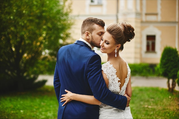 Красивый мужчина в модном синем костюме обнимает и целует красивую модельную женщину в свадебном платье