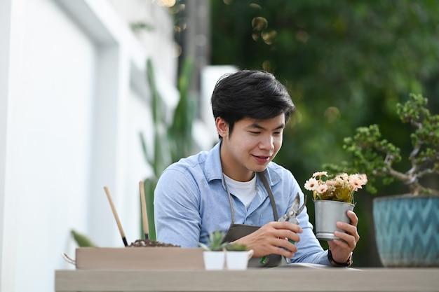 Красивый мужчина в фартуке обрезает цветы в горшке с садовыми инструментами и проводит мирное утро в садовом домике.