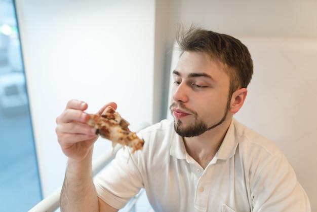 잘 생긴 남자는 그의 손에 피자 조각을 자세히 본다. 학생은 점심으로 피자를 먹는다.