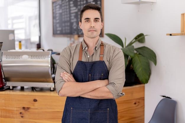 カフェに立っているハンサムな男性、彼はカフェワーカーであり、顧客にサービスを提供するために店を開く準備をしています。男性従業員は食べ物や飲み物を提供するために店を開きます。飲食サービスのコンセプト。