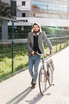 A handsome man walking with bicycle outside the building