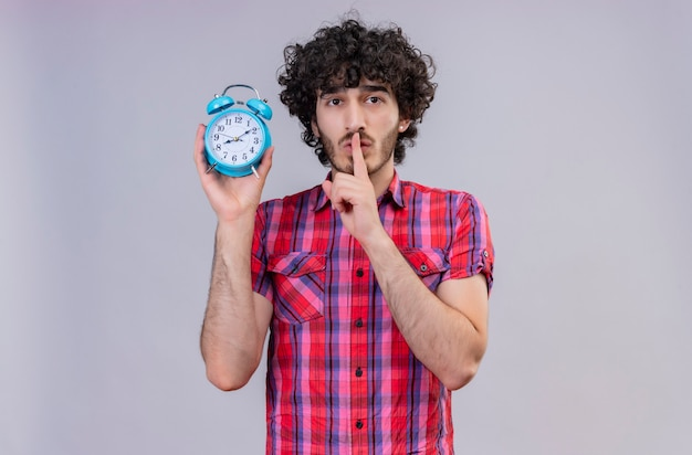Красивый мужчина с вьющимися волосами в клетчатой рубашке держит указательный палец во рту и держит синий будильник