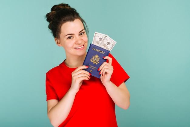 青い背景にお金のドルでパスポートを保持しているハンサムな成熟した女性-画像