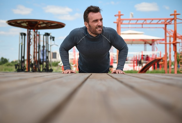 ハンサムな中年男性がシミュレーターを背景に運動場の床から押し上げ、呼気を振り返り、新鮮な空気の中で朝のトレーニングを楽しんでいます。ボディケアのコンセプト
