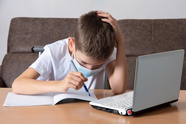 Красивый школьник в защитной маске на лице записывает информацию в свой блокнот, сидя за партой перед ноутбуком.