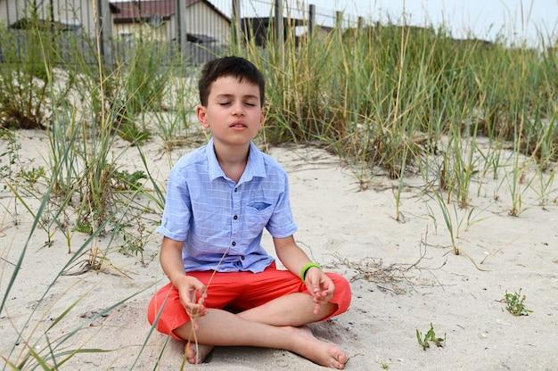 Красивый школьник в оранжевых шортах сидит на песчаном грунте в позе лотоса и спокойно медитирует на фоне природы. концепция расслабления, безмятежности и благополучия.