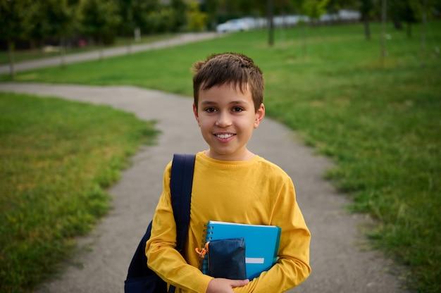 放課後の都市公園の小道には、ランドセルとノートを持ったハンサムな男子生徒が立っています。かわいい愛らしい男子生徒の肖像画