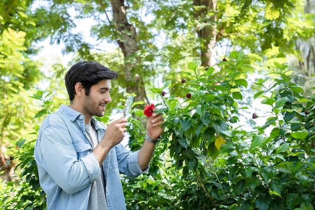 잘 생긴 과학자가 돋보기를 사용하여 정원의 붉은 꽃을 연구합니다.